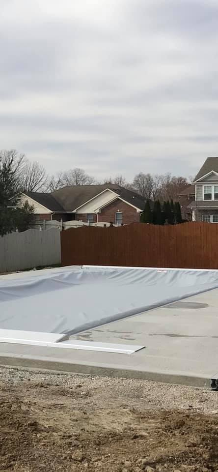 We have a free form fiberglass pool and our auto cover tracks are flush in the concrete