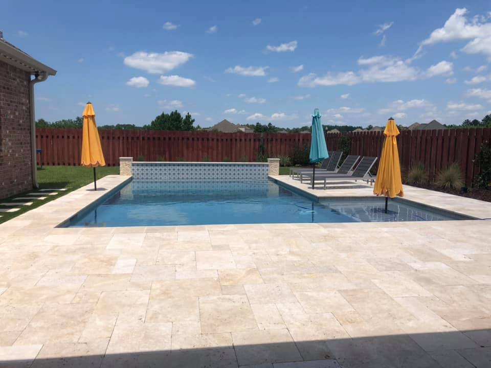 Sports bottom here. With water wall feature. Two sheer descents. Tanning ledge cut out on the side. We also have a seating ledge on both the near and far side of the pool.